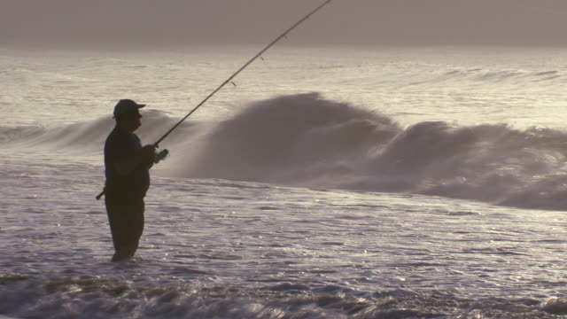 A man fishes in the ocean early morning.  The tide breaks around his legs.