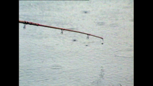 man fishes in the serpentine lake in the rain; hyde park, 1971 - lakeshore stock videos & royalty-free footage