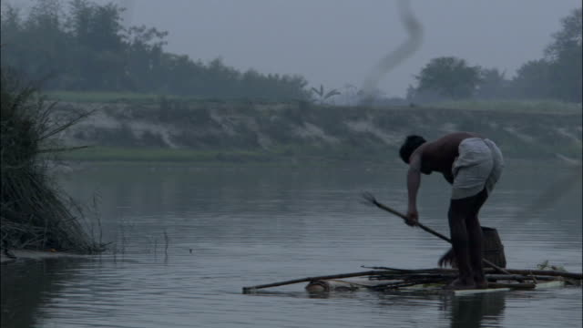 Man fishes with spear from raft Available in HD.