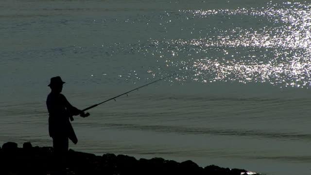 vídeos de stock, filmes e b-roll de homem pesca no bay - squiggle