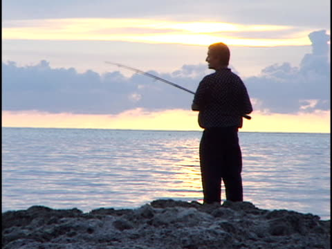 ms, man fishing at sunset, cuba - isole dell'oceano atlantico video stock e b–roll