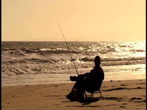 man fishing at sunset - brandungsfischen stock-videos und b-roll-filmmaterial