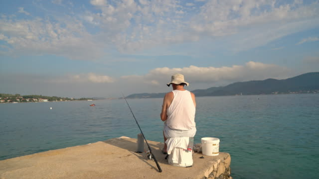 vídeos de stock e filmes b-roll de ms man fishing at the edge of sunny pier,peljesac,croatia - pescador
