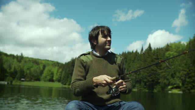 vidéos et rushes de ms man fishing from canoe on scenic lake surrounded by evergreen trees, morristown, vermont, usa - lancer la ligne de canne à pêche