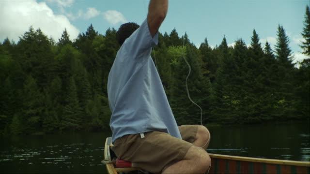 vidéos et rushes de slo mo ms man fishing from canoe on scenic lake surrounded by evergreen trees, morristown, vermont, usa - lancer la ligne de canne à pêche
