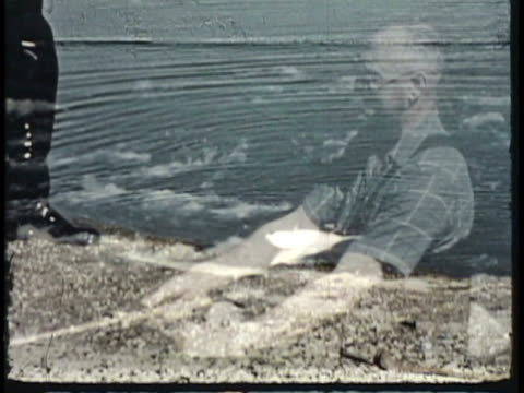 1955 montage cu ws pan ms man fishing in river, pulling fish out of water, taking hook out of fish / new zealand / audio - desaturated stock videos & royalty-free footage