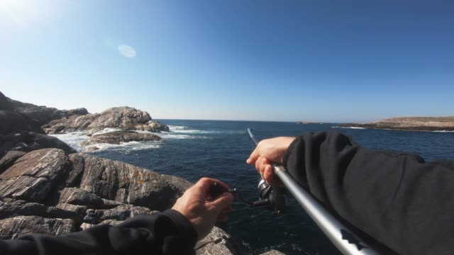 pov man fishing in the sea: catching a fish - pollock fish stock videos & royalty-free footage