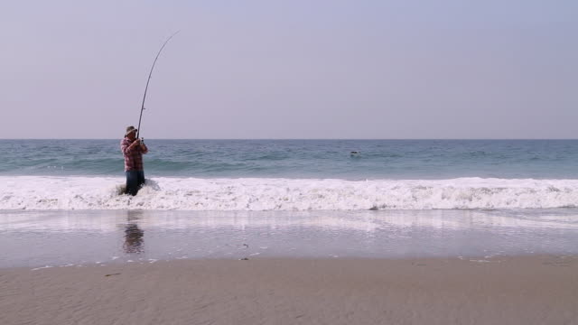 W/S Man fishing on beach.