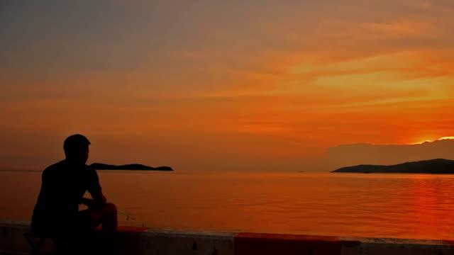 man fiskar på piren vid soluppgången. - varmt ljus bildbanksvideor och videomaterial från bakom kulisserna