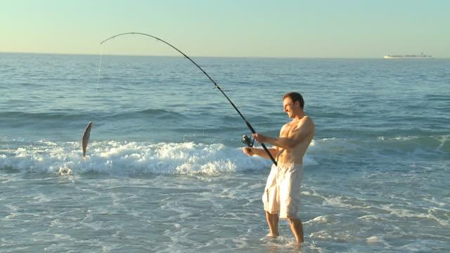 stockvideo's en b-roll-footage met ws zo pan man fishing, walking, on beach / cape town, western cape, south africa - alleen één mid volwassen man