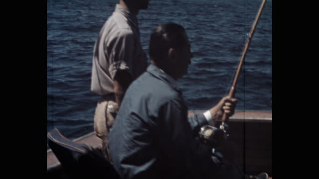 vidéos et rushes de man fishing while sitting in yacht, florida, usa - 1941