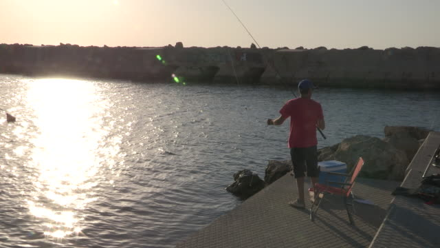 stockvideo's en b-roll-footage met man fishing while the sun begins to set - jaffa