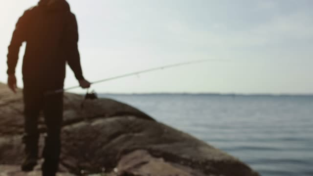 man fishing with a rod from a rock spot - fishing rod stock videos & royalty-free footage