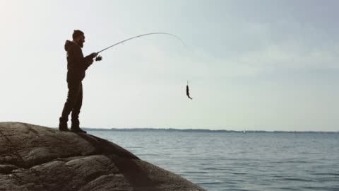 vídeos y material grabado en eventos de stock de el hombre que pesca con una varilla de un punto de roca - actividad al aire libre
