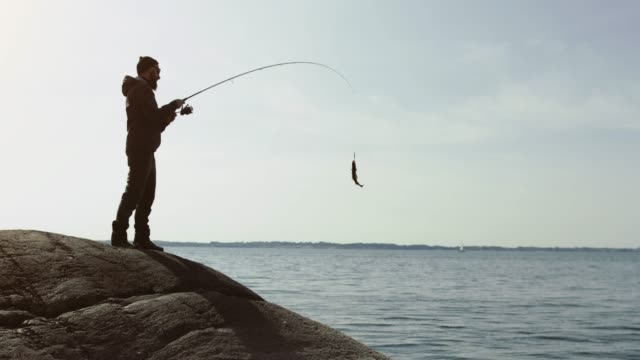 man fishing with a rod from a rock spot - outdoor pursuit stock videos & royalty-free footage
