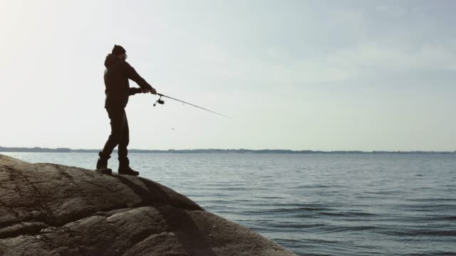 Man fishing with a rod from a rock spot