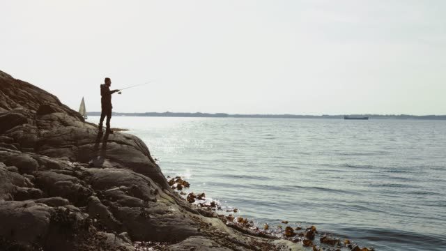 man fishing with a rod from a rock spot - fishing stock videos & royalty-free footage