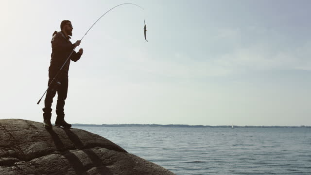 man fishing with a rod from a rock spot - catching stock videos & royalty-free footage