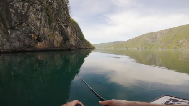 vídeos de stock e filmes b-roll de pov man fishing with a rod from a small boat in the sea by a fjord, in norway - captura de peixe