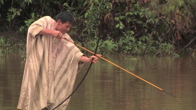 MS man fishing with bow and arrow/ Manu National Park, Peru