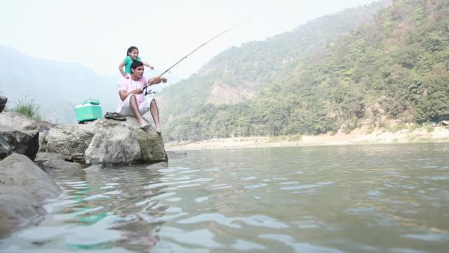 vídeos y material grabado en eventos de stock de man fishing with his daughter at riverbank  - nevera portátil