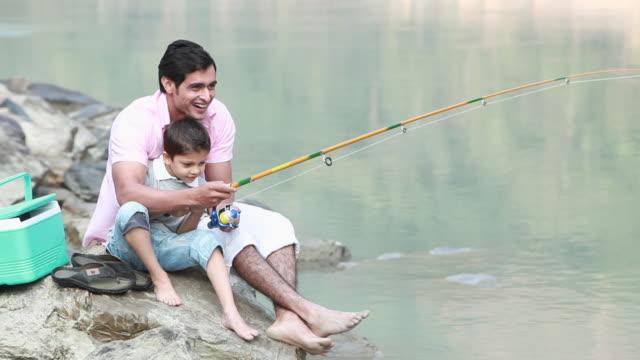Man fishing with his son at riverbank