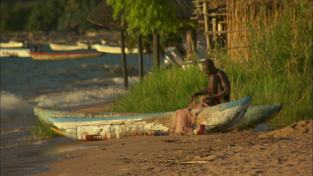 A man fixes a fishing net on the shoreline of Lake Malawi.