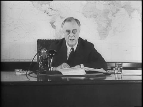 Man fixes light on President Franklin D Roosevelt / FDR sitting at desk in profile with large map of world in background / Press and camera men...