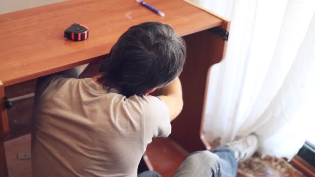 Man fixing a desk on his own at home