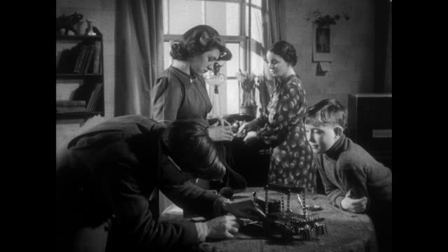 montage man fixing a toy tractor for a boy while they converse with two women / east anglia, united kingdom - 1940 stock videos & royalty-free footage