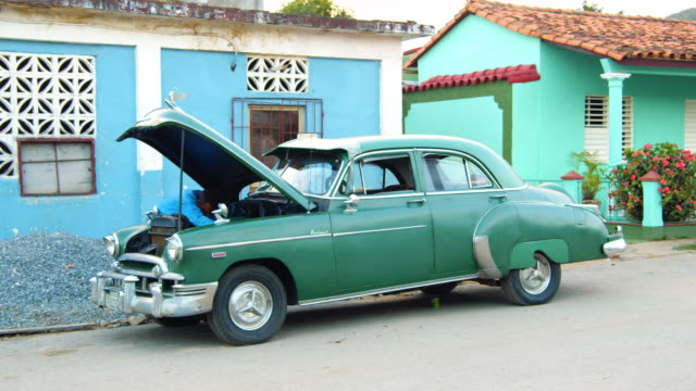 man fixing his vintage car on a street in trinidad, cuba - communism stock videos & royalty-free footage