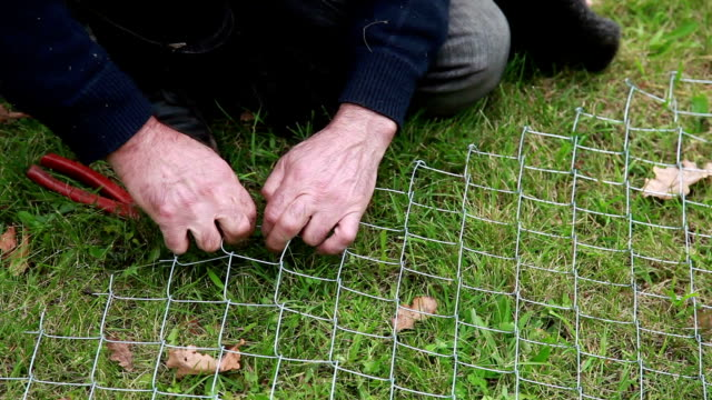 man fixing wire fencing on the grass - chainlink fence stock videos and b-roll footage
