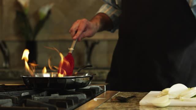 vídeos de stock, filmes e b-roll de cu pan man flambeing at stove, mid section / orem, utah, usa - espátula