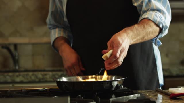 cu man flambeing at stove, mid section / orem, utah, usa - orem utah stock videos & royalty-free footage
