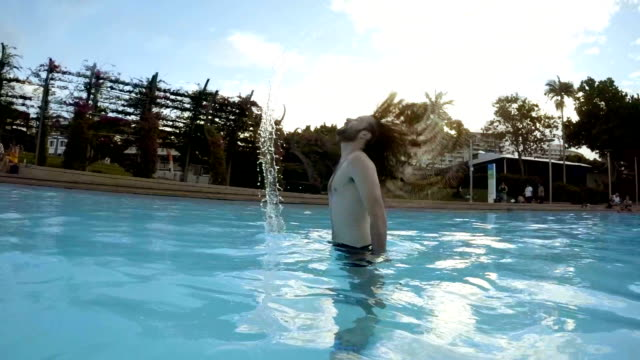 man flicking his long hair in the pool - hair toss stock videos & royalty-free footage