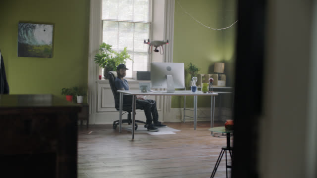 slo mo. man flies his drone inside his home office. - wide shot stock videos & royalty-free footage