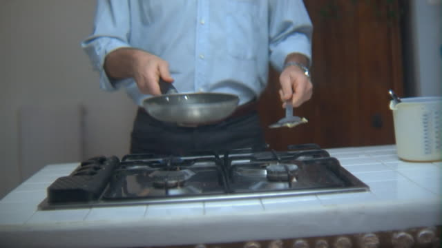 ms man flipping pancakes in pan over stove/ tu man smiling/ rome, italy - 投げる点の映像素材/bロール