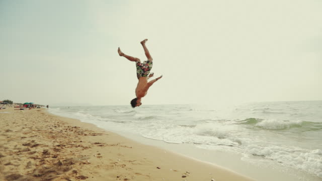 vídeos de stock e filmes b-roll de man flips and spins a sommersault on the beach - girar