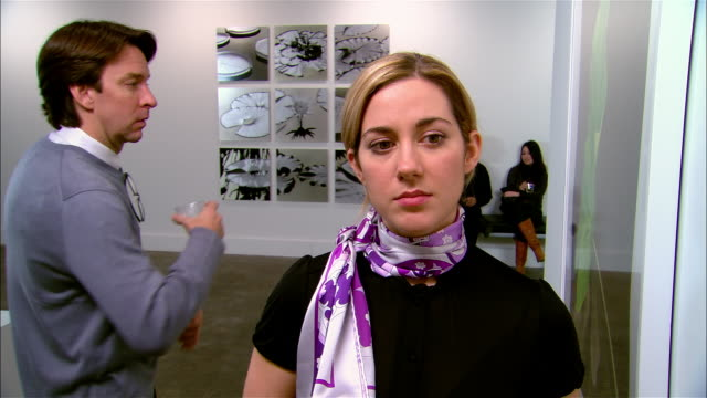 Man flirting with woman looking at artwork at gallery opening / she rejects him / he walks away and she smiles