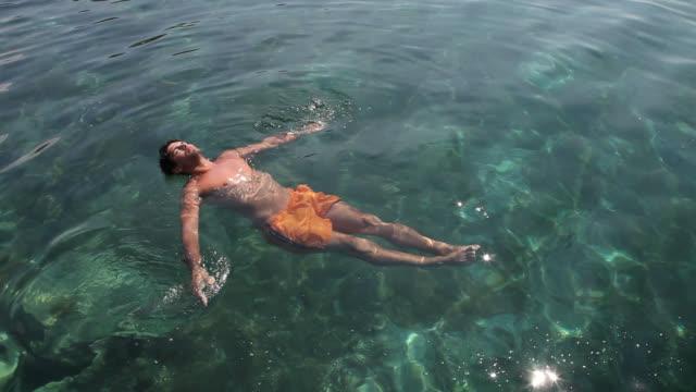 vídeos y material grabado en eventos de stock de man floats in the sea - calzoncillos bóxer