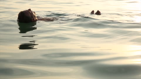 man floats in tropical sea, at sunrise - one mature man only stock videos & royalty-free footage