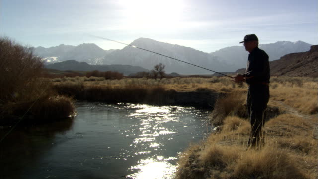 a man fly fishes in a stream near the sierra nevada mountains. - californian sierra nevada stock videos & royalty-free footage