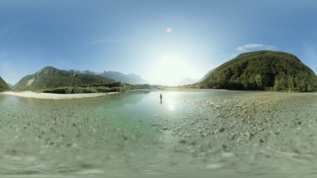 AERIAL VR 360: Man fly fishing in sunshine