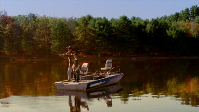 vídeos de stock, filmes e b-roll de ms, man fly fishing standing by grandson (10-11 years) on fishing boat on lake, usa, pennsylvania - 10 11 years
