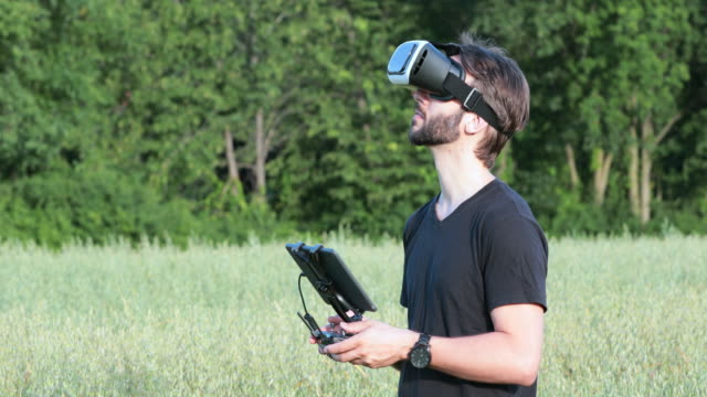 man flying a drone with virtual reality goggles headset - piloting stock videos and b-roll footage