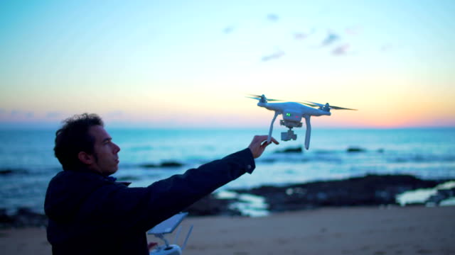 man flying dron at sunset in the beach - remote control video stock e b–roll