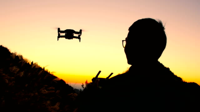 vídeos de stock e filmes b-roll de man flying drone at sunset - pairar