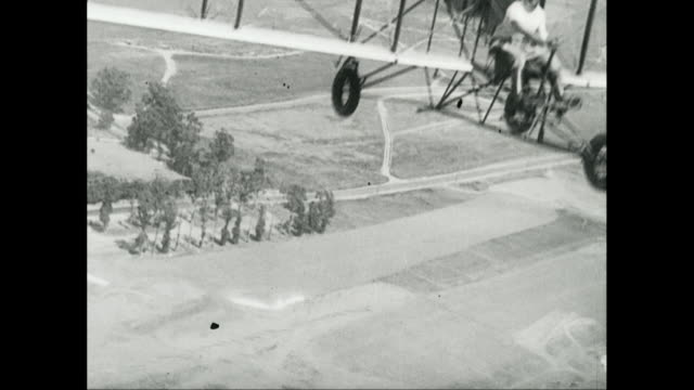 ws aerial pov man flying early biplane over landscape / united states - anno 1940 video stock e b–roll