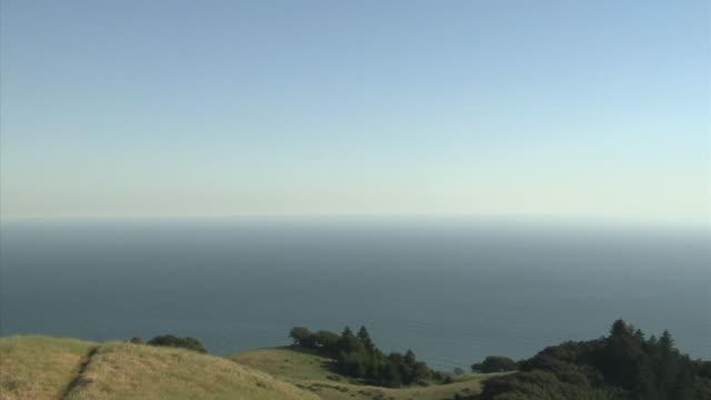 WS PAN Man flying kite on hill overlooking sea, Mount Tamalpais, California, USA