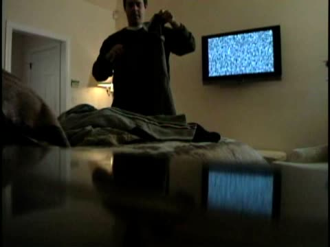 la ms man folding his clothes while static appears on flat screen television on wall behind him / white plains, new york, usa - flat screen stock videos & royalty-free footage